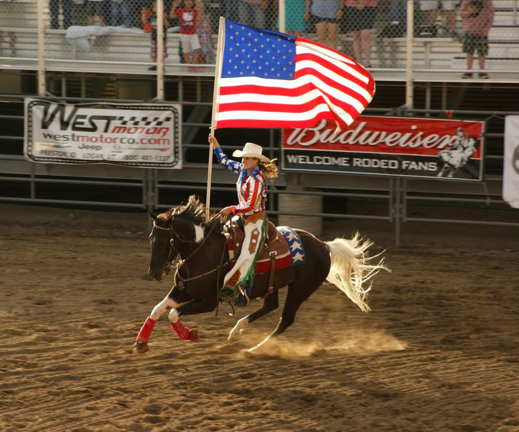 Man riding horse holding us a flag